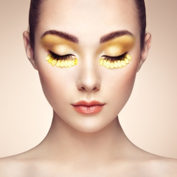 Face of beautiful woman decorated with flowers Perfect makeup Beauty fashion Eyelashes Cosmetic Eyeshadow